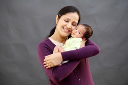 Cheerful mother and newborn baby