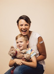 Cheerful mother and son after vaccination on brown background. Woman holding her son with a teddybear.