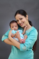 Cheerful mother holding newborn baby