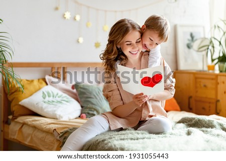 Cheerful mother hugging son and reading handmade greeting card with heart while resting on bed during holiday celebration mothers day  at home