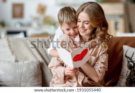 Cheerful mother hugging son and reading handmade greeting card with heart while resting on sofa during holiday celebration mothers day at home