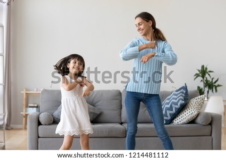 Cheerful mother little daughter standing in living room at home moving dancing to favourite song together. Child have fun with elder sister nanny or loving mother active leisure and lifestyle concept