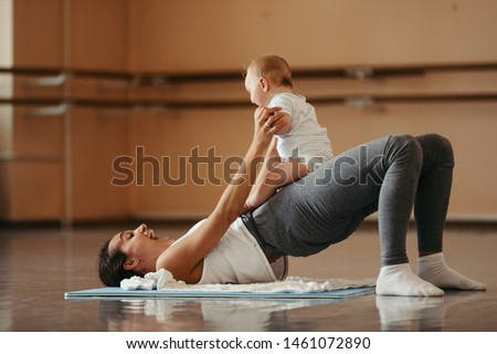 Cheerful mother working out and having fun with her baby in health club.