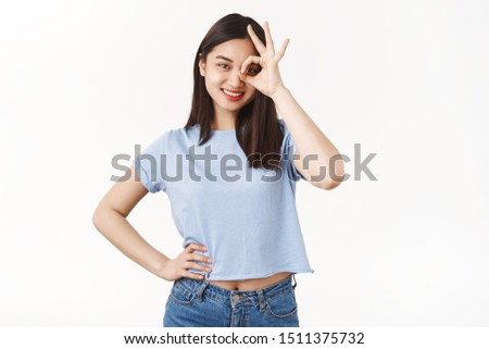 Cheerful motivated assertive cute asian female show okay ok excellent gesture circle on eye look through emotive agree like perfect skincare helpful products really works stand white background