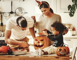 Cheerful multi ethnic family parents with son smiling  while creating jack o lantern from pumpkin during Halloween celebration in kitchen at home