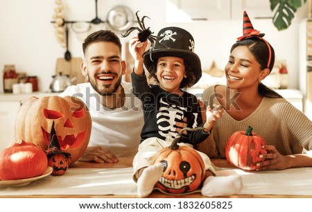 Cheerful multi ethnic family parents with son smiling  while creating jack o lantern from pumpkin during Halloween celebration in kitchen at home Foto stock ©