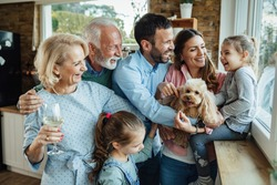 Cheerful multi-generation family with a dog having fun while spending time together at home.