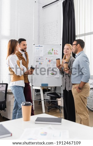 Cheerful multiethnic businesspeople with takeaway drink working near charts on flipchart stock photo
