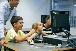 Cheerful multiethnic children having fun at lesson and learning with help of teacher. Happy adorable boy and girls using computer at school and smiling. Informatics and education concept