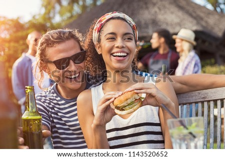 Cheerful multiethnic couple enjoying hamburger and beer at barbecue party. Happy young black woman eating burger while is sitting on boyfriend legs. Joyful guy and girl having fun at bbq party.