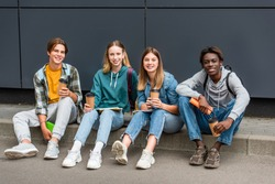 Cheerful multiethnic teenagers with coffee to go and notebooks looking at camera on sidewalk near building