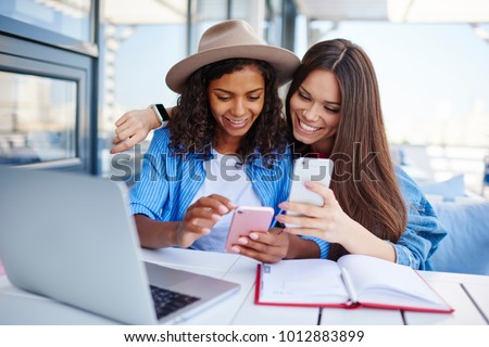 Cheerful multiracial female best friend share multimedia files on smartphones spending free time together,smiling hipster girls synchronizing telephone sending photos and video sitting at cafe