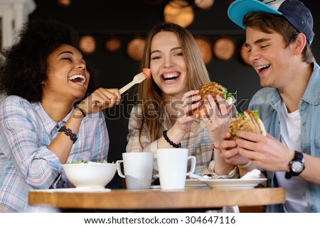 Cheerful multiracial friends eating in a cafe  #304647116