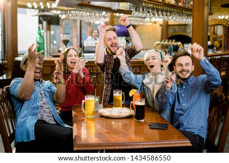 Cheerful multiracial friends having fun eating in pizzeria. They are watching football match emotionally stock photo