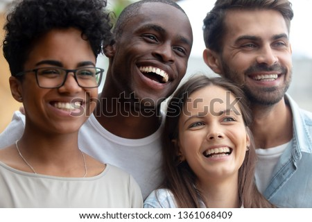 Photo of Cheerful multiracial millennial happy best friends gathering outdoors laughing looking away posing for photo, smiling multicultural diverse young people group having fun embracing celebrating reunion
