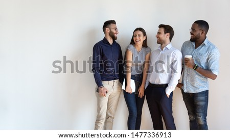 Cheerful multiracial professional business people laughing together standing in row near wall, happy diverse young employees students group, corporate staff team having fun, human resource concept