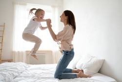 Cheerful mum babysitter play with cute active small kid girl jump on bed, happy carefree mother and little child daughter holding hands laughing having fun feel joy at home in modern bedroom interior
