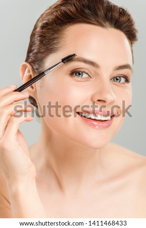 cheerful naked woman shaping eyebrow with eyebrow brush and smiling isolated on grey
