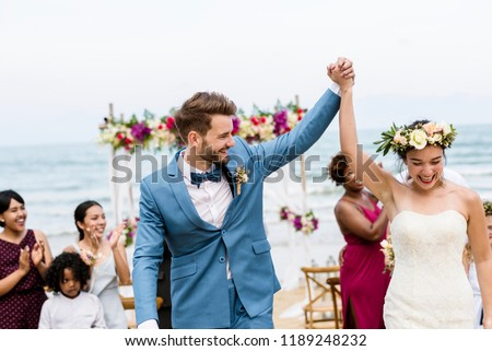 Cheerful newlyweds at beach wedding ceremnoy