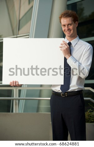 Cheerful office worker in white dress shirt, tie, slacks holding blank placard to his side outside office building exterior.  Custom text insert. 20s handsome caucasian British male looking at camera