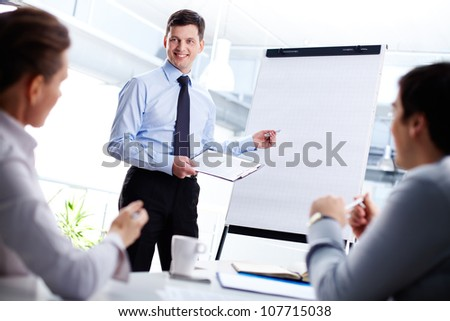 Cheerful office worker pointing at the blank whiteboard making a presentation - stock photo