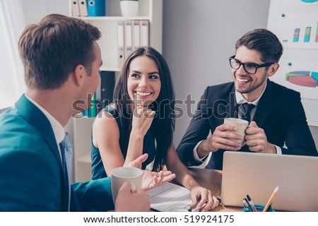 Cheerful office workers  discussing their project over cup of tea