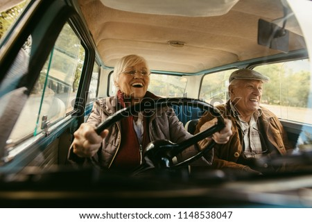 Cheerful old couple driving in a car. Enjoying road trip. Senior woman driving car with woman enjoying the ride and laughing.