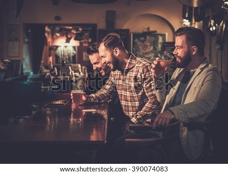 Cheerful old friends having fun and drinking draft beer at bar counter in pub.