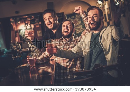 Cheerful old friends having fun watching a football game on TV and drinking draft beer at bar counter in pub.