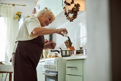 Cheerful old lady adding salt to soup and smiling while standing by the stove with cooking pots