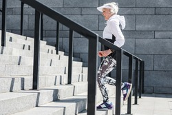 Cheerful old lady training to run up concrete stairs