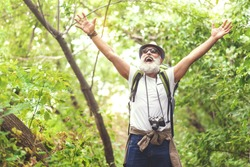 Cheerful old man feels freedom while traveling in forest