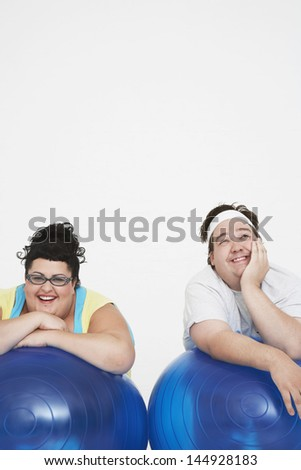Cheerful overweight man and woman resting on exercise ball against white background