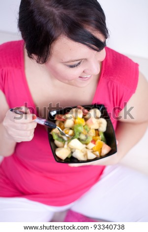 Cheerful overweight woman eating a fruit salad