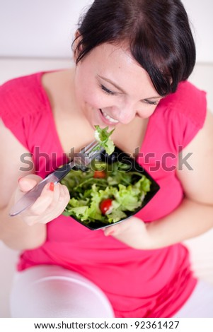 Cheerful overweight woman eating a salad. Selective focus.