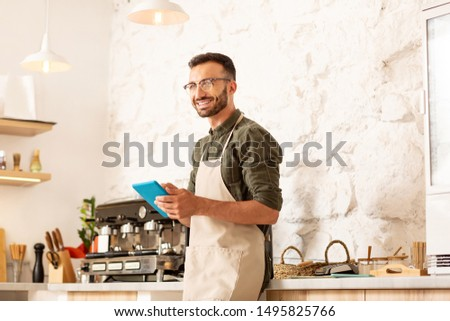 Cheerful owner. Cheerful owner of coffee shop smiling while holding little tablet and working all day long #1495825766