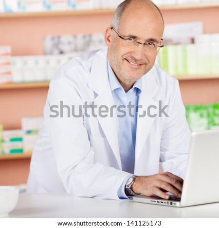 Cheerful pharmacist browsing the internet using laptop in drugstore