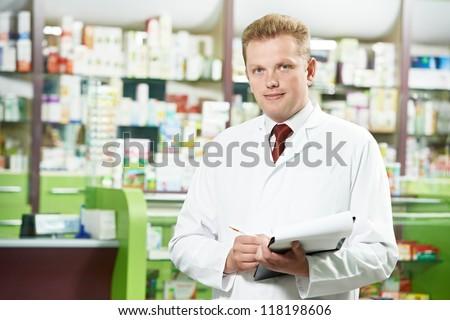cheerful pharmacist chemist man standing in pharmacy drugstore