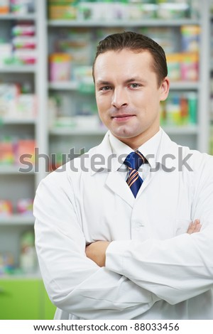 cheerful pharmacist chemist man standing in pharmacy drugstore