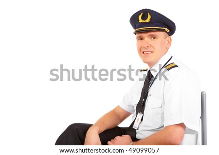 Cheerful pilot wearing uniform with epaulets and hat with golden wings, sitting, isolated on white background.