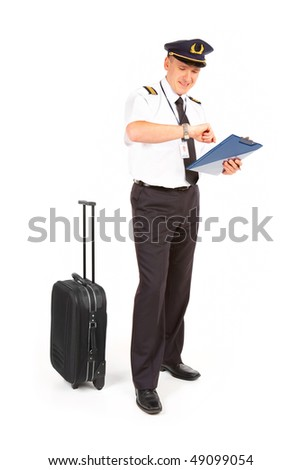 Cheerful pilot wearing uniform with epaulets standing with trolley bag and documents, checking time isolated on white background.