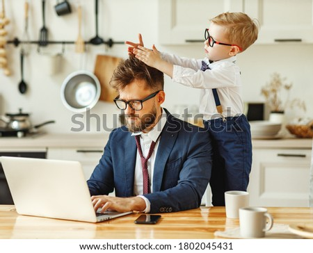 Cheerful playful kid sitting on neck of unhappy busy dad in formal wear during phone conversation and working with laptop in home kitchen