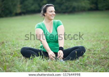 Cheerful plus sized woman stretching in the park. Selective focus.