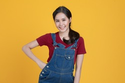 Cheerful portrait close up half-length shot of beautiful Asian woman in a denim dungarees. She put her hand on hip  with confidence in herself isolated on yellow background.