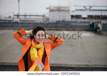 Cheerful portrait of gorgeous girl with black curly hair in orange cloak and varicolored bright scarf. Bright girl walking on gray river port. Happy gaze of beautiful female eyes. Girl is fun. #1095349850
