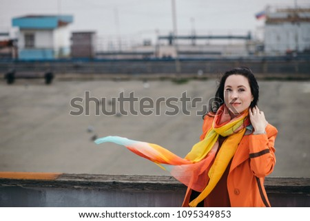 Cheerful portrait of gorgeous girl with black curly hair in orange cloak and varicolored bright scarf. Bright girl walking on gray river port. Happy gaze of beautiful female eyes. Girl is fun. #1095349853