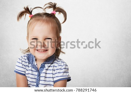 Cheerful positive adorable small child with two pony tails, dressed in striped t shirt, expresses pleasant emotions, being glad to recieve new toy from parents, isolated on white wall, copy space #788291746