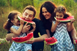 Cheerful positive family of four having a picnic and eating watermelon outdoors in a sunny weather. Curly beautiful twins sisters eating a snack lunch. Vegetarian Concept.