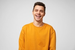 Cheerful positive male youngster, dressed casually, glad to spend time with friends, joking laughing, has a good time. Positive emotions and feelings, isolated over white background