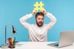 Cheerful positive man blogger with beard in white shirt holding yellow hashtag sign above head, explaining how to tag posts in social network, keywords. Indoor studio shot isolated on blue background